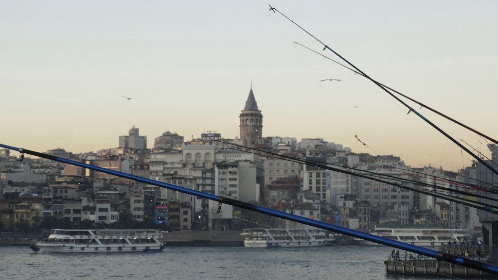 Fishing from Galata Bridge with a view of Galata Tower in Istanbul